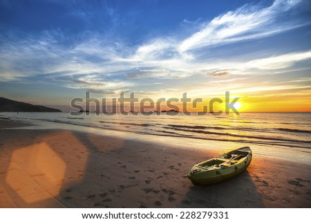 Tropical landscape. Canoe on the ocean beach during the amazing sunset. - stock photo