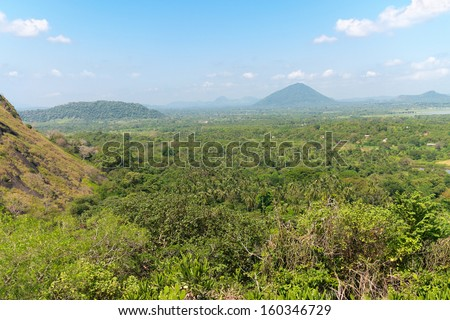 Tropical landscape with hill and mountain under blue sky, Dambulla, Sri Lanka  - stock photo