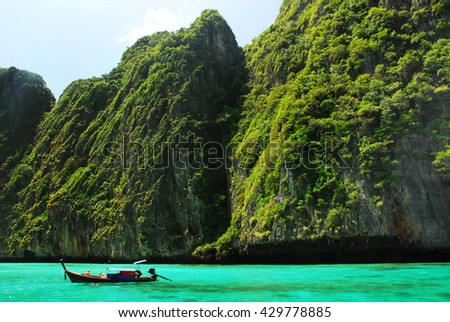 Tropical landscape with rock islands, lonely boat and crystal clear - stock photo