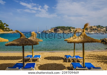 Tropical lounge chairs and umbrellas on a sandy resort beach in Port de Soller, Mallorca, Spain. - stock photo