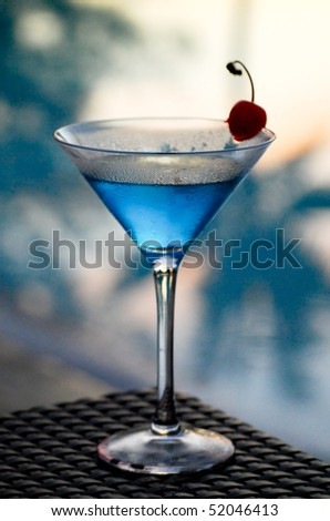 Tropical martini cocktail against a poolside background at sunset - stock photo