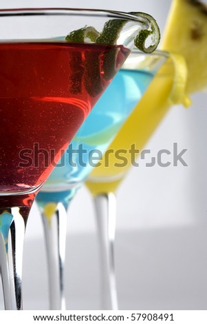Tropical Martini style drinks with fruit & garnish - stock photo