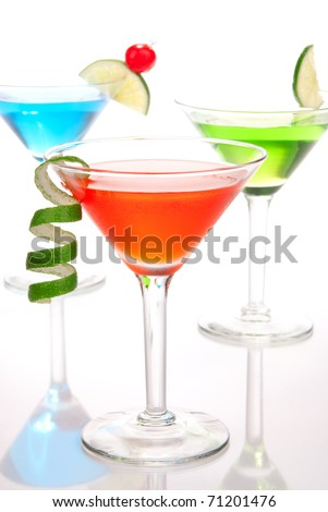 Tropical martinis Cocktails with vodka, light rum, gin, tequila, blue curacao, lime juice, lemonade, lemon slice, maraschino cherry in martini glass on a white background - stock photo