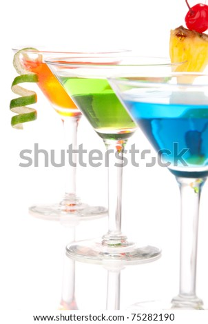 Tropical martinis Cocktails with vodka, light rum, gin, tequila, blue curacao, lime juice, lemonade, lemon slice, maraschino cherry in martini glass on a white background. Focus on green cocktail - stock photo