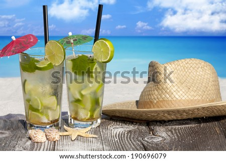 Tropical Mojito Cocktail on Wooden Boards with a Straw Hat, Starfish and Sea Shell on the Beach with Copy Space for additional information