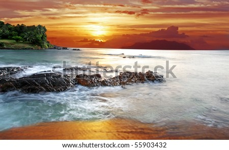 Tropical Nights with long Exposure to create a dreamy Milky white Indian Ocean in The Seychelles with Silhouette Island at Sunset - stock photo