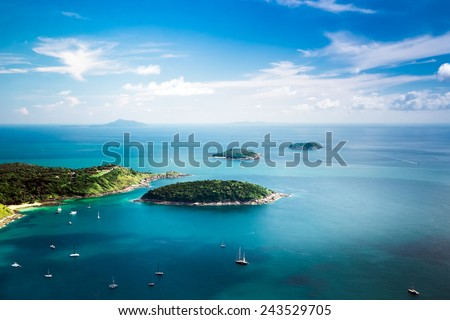 Tropical ocean landscape with Koh Kaeo island at turquoise ocean waives with boats near Ya Nui beach. Rawai, Phuket, Thailand