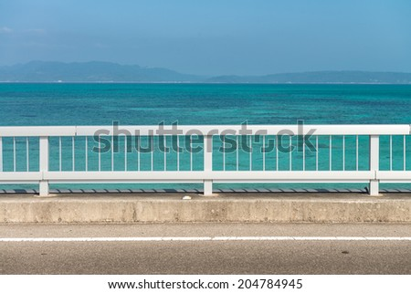 Tropical ocean with fence and road - stock photo