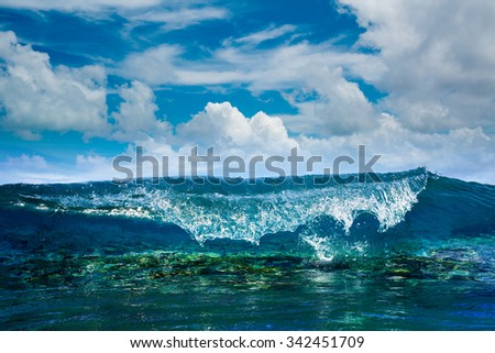 Tropical ocean with shorebreak. Surfing wave splashing on coral reef. Maldivian paradise with clouds on blue sky in daylight.