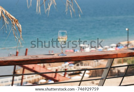 Tropical palm branches reflected in white wine glass on Dead Sea beach background