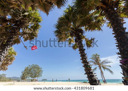 tropical palm trees on white sand beach and Parasailing extreme sports on beach in kata beach phuket thailand ,summer nature view for background  - stock photo