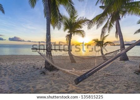 Tropical paradise beach at sunset with hammock - stock photo