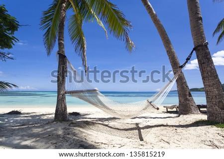 Tropical paradise beach with hammock - stock photo