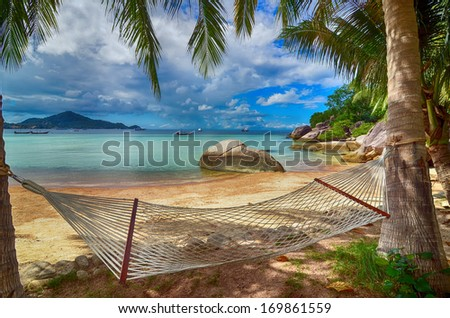 Tropical Paradise - Hammock at the lovely beach at the seaside between palm trees with the view to the blue water - stock photo