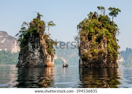 Tropical paradise in Thailand. Boat in a lake between rocks in National Park. - stock photo