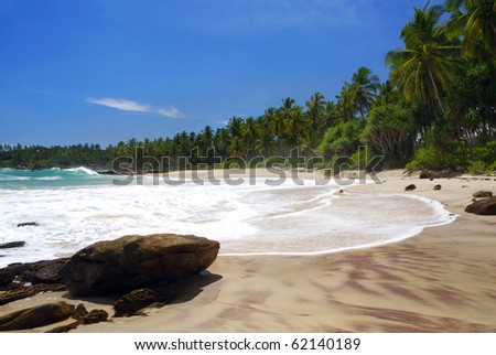 Tropical paradise on Sri Lanka with palms hanging over the white and red beach, turquoise sea and boulders in the front - stock photo