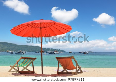 Tropical paradise on the shores of the azure sea. Red beach umbrella and deck chairs on the white sand - stock photo