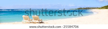 Tropical Paradise. Panorama of tropical white sand beach with sun beds. - stock photo