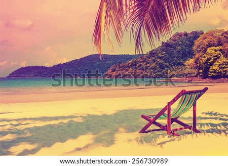 Tropical paradise. Seaside view of the tropical island with beach chair on white sand beach. Summer travel concept background with retro vintage instagram filter. - stock photo