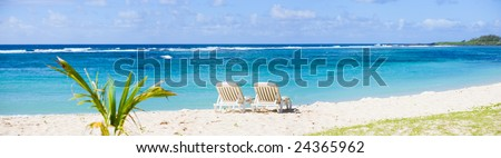 Tropical Paradise. Sun beds on tropical white sand beach. - stock photo