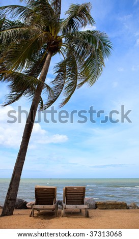 Tropical Paradise. Two sun beds on exotic beach. - stock photo