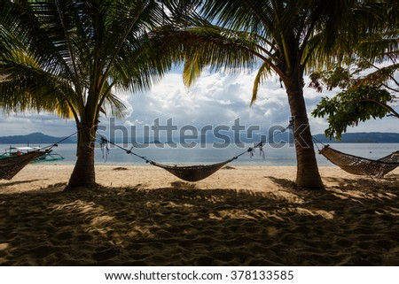 Tropical paradise with hammocks and palm trees - stock photo