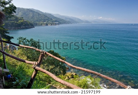 Tropical Puerto Vallarta, Mexico from shore behind a rustic wooden fence - stock photo