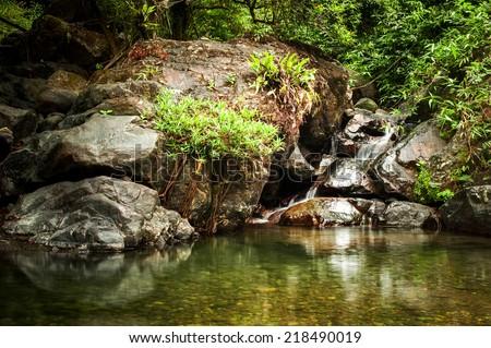 Tropical rainforest landscape with beautiful lake, small waterfall, rocks and jungle plants. Vang Vieng, Laos - stock photo