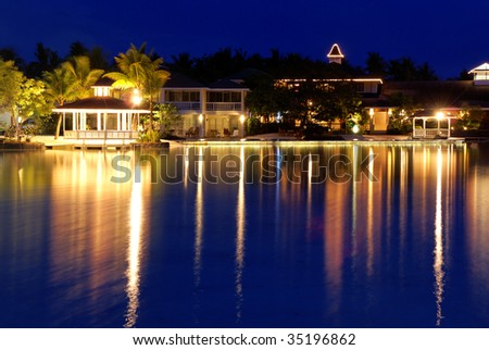 Tropical resort at dusk with reflection on the sea - stock photo
