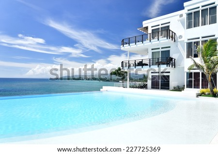 Tropical resort hotel infinity pool with seascape view - stock photo