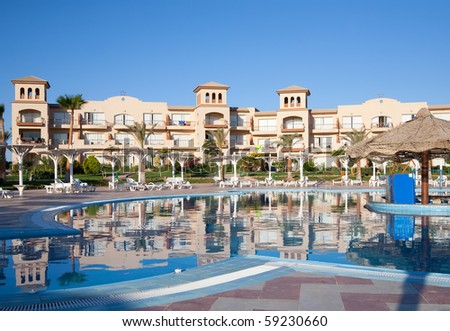 Tropical resort hotel with beautiful pool in foreground - stock photo