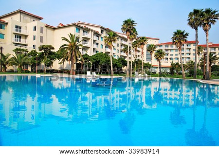 Tropical resort hotels with beautiful pool in foreground - stock photo