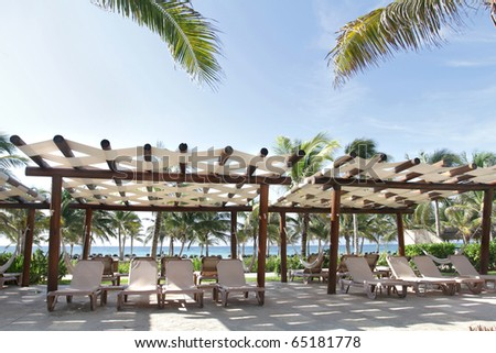 Tropical resort on empty white sand beach, ocean and palm trees in Mexico, Riviera Maya
