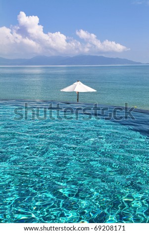 Tropical resort. Poolside with beautiful sea view - stock photo