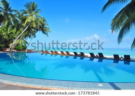 tropical resort swimming pool overlooking sea - stock photo