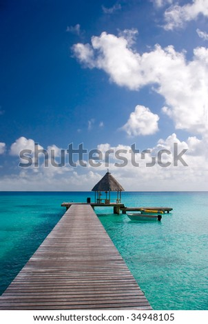 tropical resort vacation dock pier in tahiti with boat and turquoise water