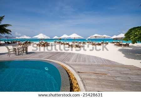 tropical resort with beach chairs and swimming pool right at the beach - stock photo