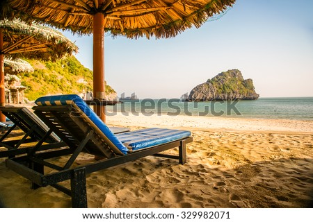 Tropical resort with chaise longs under palms on sandy beach, rocky island seen in distance - stock photo