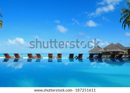 Tropical resorts swimming pool and cafe bar near the beach -- Maldives tropical island resorts - stock photo