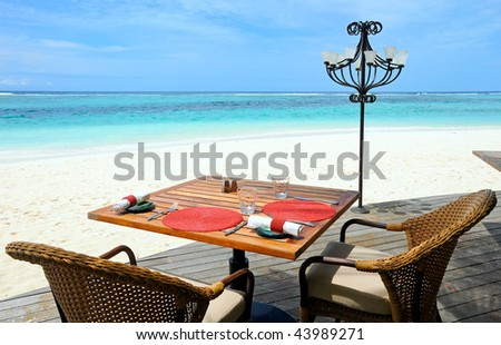 tropical restaurant on the beach with view over turquoise ocean - stock photo