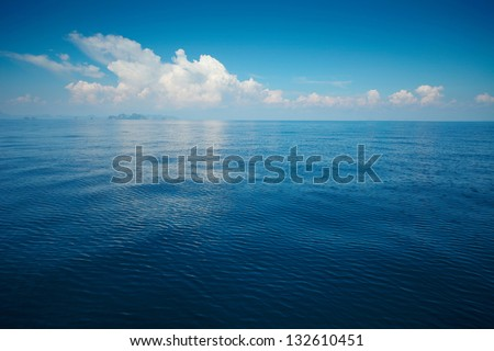 Tropical rippled and calm sea with far islands on the horizon and white fluffy clouds - stock photo