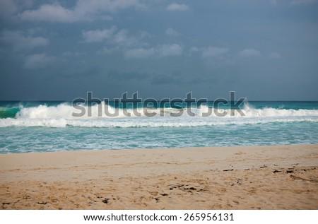 Tropical sand beach of Caribbean sea under gloomy sky - stock photo