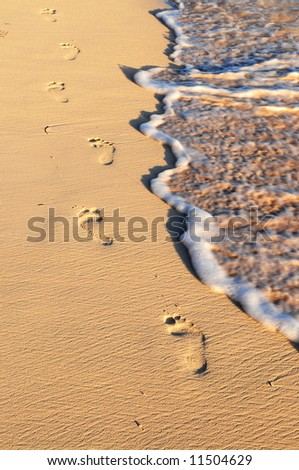 Tropical sandy beach with footprints and ocean wave - stock photo
