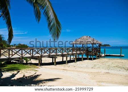 Tropical sandy beach with palm trees and pier. Holiday, relaxation and rest. Fiji - stock photo