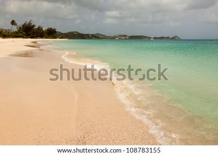 Tropical Sandy Caribbean Beach with Cloudy Overcast Sky Antigua - stock photo