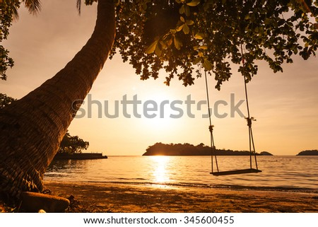 Tropical sea beach with swing tied at sunset - stock photo