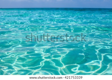 Tropical sea water with bright sun light reflections - stock photo