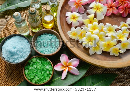 Tropical setting on mat with many frangipani,salt in bowl