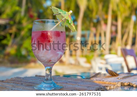 tropical shake, refreshment drink in decorated glass on tropical background