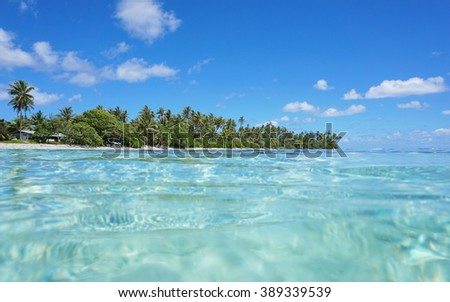 Tropical shore with turquoise water near Maeva village of Huahine island, seen from the ocean surface in the lagoon, Pacific, French Polynesia - stock photo